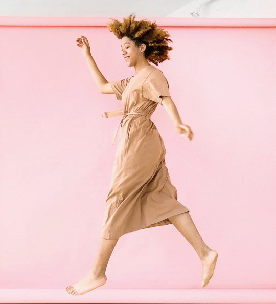 Woman wearing brown dress jump near pink wall 1179141 2